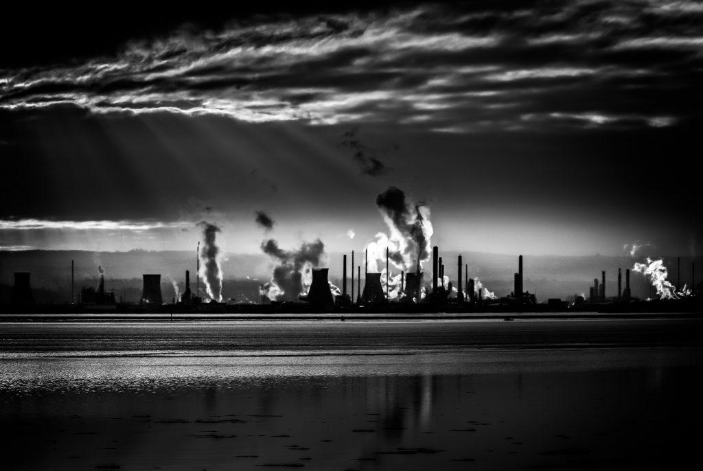 Ciudad contaminada en blanco y negro con nubes y chimeneas de fábricas al fondo y un mar calmado en primer plano